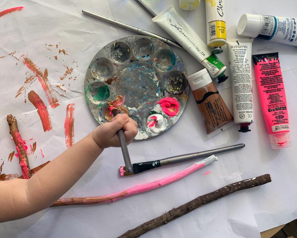 Bird's eye view of child holding paint brush and painting sticks
